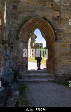 Woman stood in an arched door way at Bolton Abbey,Skipton,North Yorkshire,England. - Stock Photo