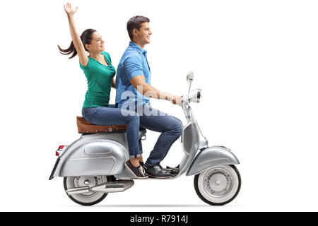 Full length profile shot of a young couple riding on a vintage motorbike and waving isolated on white background - Stock Photo