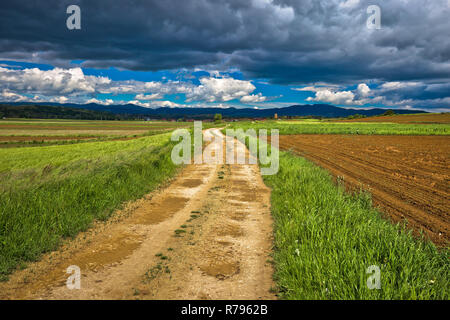 Dirt road under cloudy sky view, stormy landscape of Prigorje region in Croatia - Stock Photo