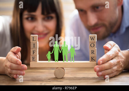 Couple Protecting Balance Between Work And Life On Seesaw - Stock Photo