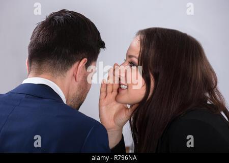 Businesswoman Whispering Into Partner's Ear - Stock Photo