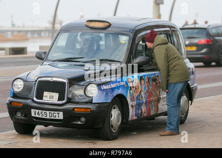 London type Black cab on the streets of Blackpool, UK carrying sponsored advertising. - Stock Photo