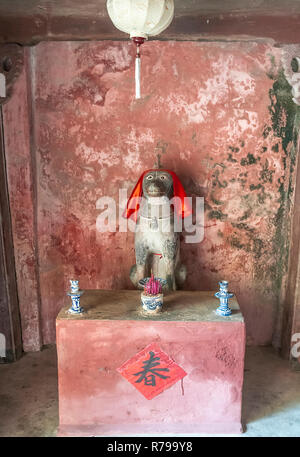 Shrine with statue of a dog inside Hoi An's 18th century Japanese wooden covered bridge, Hoi An, Vietnam, Quang Nam Province, South East Asia - Stock Photo