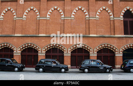 Profile of a row of black cabs or taxis on a London street in front of a city building with copy space - Stock Photo