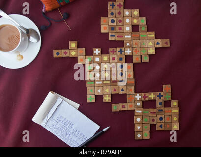 A board game on a table with scores written down and a cup of coffee - Stock Photo