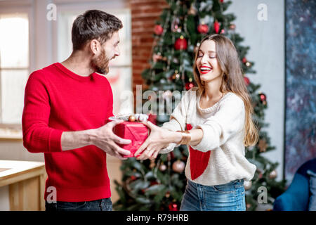 Man giving a New Year gift for a young excited woman standing near the Christmas tree at home - Stock Photo