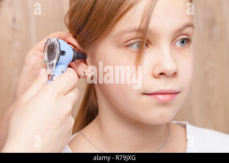 Female pediatrician examines elementary age girl's ear. Doctor using a otoscope or auriscope to check ear canal and eardrum membrane. Child ENT check  - Stock Photo