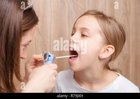 Female pediatrician or health care practitioner examines elementary age girl's throat using wooden tongue depressor and torch. Child physical examinat - Stock Photo