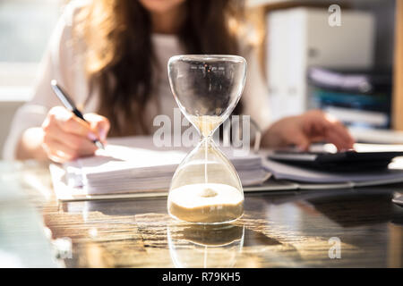 Close-up Of A Hourglass On Desk - Stock Photo