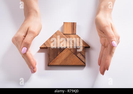 Woman Protecting House Made Of Wooden Tangram Puzzle - Stock Photo