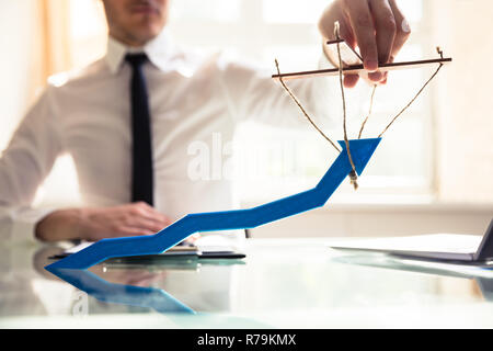 Businessperson Manipulating Blue Arrow - Stock Photo