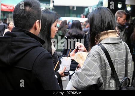 Young Chinese people tourists eating snack food, brownies at outdoor street food Borough Market in Southwark South London UK   KATHY DEWITT - Stock Photo