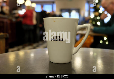 Cafe Nero coffee cup on a table inside shop store interior and blurred Christmas tree decorations in Cardiff Wales UK. KATHY DEWITT - Stock Photo