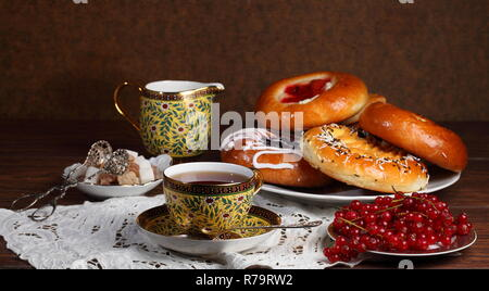 Still life with tea, denish and red currants - Stock Photo