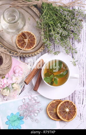 Still life with tea with cinnamon, mint, thyme on a wooden table - Stock Photo