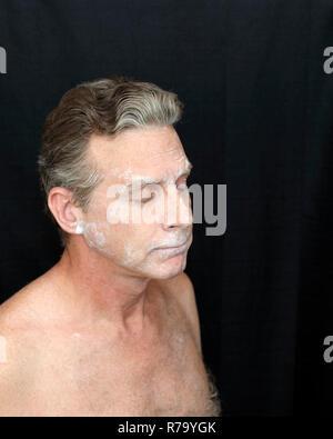 Mature Male Wearing Thin Bentonite Clay Face Mask - Stock Photo