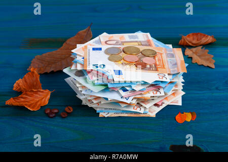 A lot of euro banknotes and coins with leaves and coffee beans on blue background. - Stock Photo