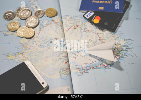 The plane, smartphone, biometric passport, dollars, coins and credit cards lie on a map of Iceland - Stock Photo