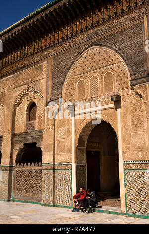 Morocco, Fes, Fes el Bali, Medina, Talaa Seghira, Medersa Bou Inania, young tourists sat in door - Stock Photo