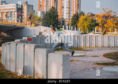 Parkour man training jumping over high concrete wall at urban place - Stock Photo