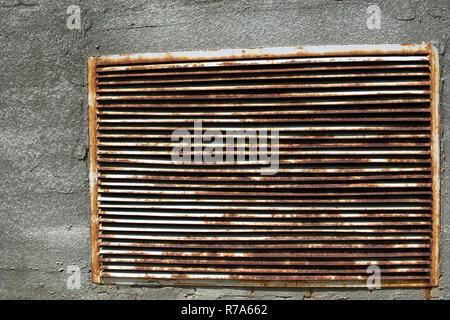 A brick wall with a rusty iron grille - Stock Photo