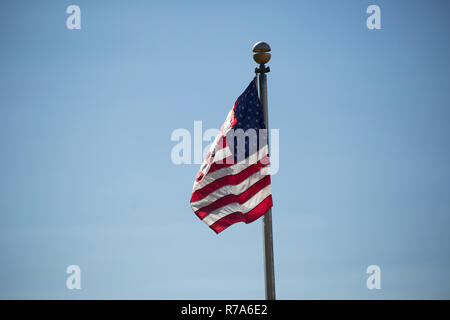 American flag waving vigorously in the wind against a blue sky - Stock Photo