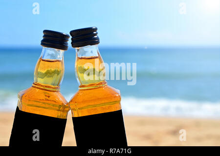 Two little bottles whiskey  stand on the sand closeup. Alcoholic party in a nautical style on the shores of the Atlantic Ocean. - Stock Photo