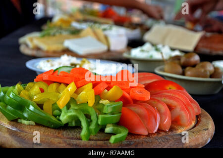 sliced from different peppers, carrots, tomatoes, olives, soft and hard cheese on wooden board. Snack from different types of cheese, olives and veget - Stock Photo