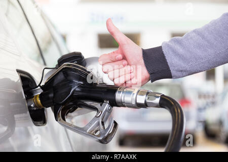 Petrol or gasoline being pumped into a motor vehicle car. Closeup of man, showing thumb up gesture, pumping gasoline fuel in car at gas station. - Stock Photo
