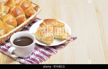 Fresh croissants on a plate, a cup of coffee - Stock Photo