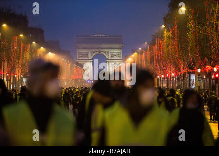 Paris, France. 8th Dec 2018. Protesters seen walking peacefully on the Champs-Elysées during a 'Yellow Vest' protest in Paris. Without any political affiliation, the 'Yellow Vest' movement rallies in various cities in France this saturday against taxes and rising fuel prices. Credit: SOPA Images Limited/Alamy Live News - Stock Photo