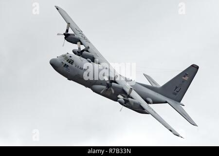 A C-130H Hercules assigned to the 36th Airlift Squadron flies over Combined Armed Training Center Camp Fuji, Japan, April 12, 2017, during a training mission. Airmen from the 374th Logistics Readiness Squadron and Eagle airlifts with the 36th AS conducted mass containerized delivery system airdrop training. - Stock Photo