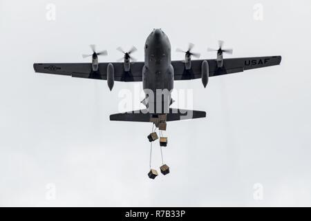 Airmen inside a C-130H Hercules assigned to the 36th Airlift Squadron drops containerized delivery system bundles at Combined Armed Training Center Camp Fuji, Japan, April 12, 2017. Airmen from the 374th Logistics Readiness Squadron and Eagle airlifts with the 36th AS conducted mass CDS airdrop training. - Stock Photo