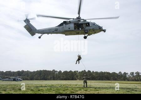 "VIRGINIA BEACH, Va. (April 12, 2017) — An Explosive Ordnance Disposal technician, assigned to Explosive Ordnance Disposal Group (EODGRU) 2, rappels from an MH-60S Sea Hawk helicopter, assigned to the ""Nightdippers' of Helicopter Sea Combat Squadron 5, during helicopter rope suspension technique (HRST) training at Joint Expeditionary Base Fort Story. EODGRU 2 is headquartered at Joint Expeditionary Base Little Creek-Fort Story and oversees Mobile Diving and Salvage Unit Two (MDSU 2) and all east coast based Navy EOD mobile units. - Stock Photo"