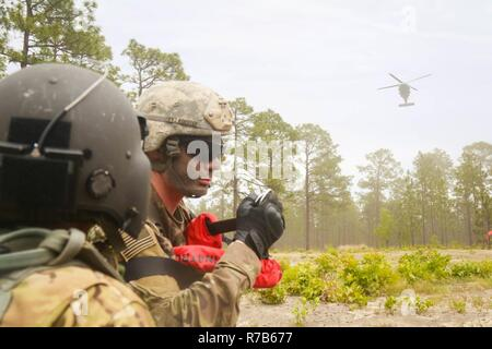 An HH-60 Black Hawk helicopter assigned to Charlie Company, 'All-American DUSTOFF,' 3rd General Support Aviation Battalion, 82nd Combat Aviation Brigade approaches flight medic, Army Staff Sgt. McNeill  with a simulated casualty for extraction during Medevac training on Griffin helicopter landing zone at Fort Bragg, N.C., May 9. - Stock Photo