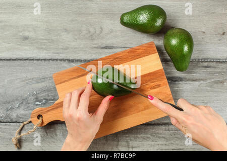Tabletop view, woman hands holding knife, cutting green whole avocado on chopping board. - Stock Photo