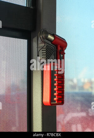 Red hammer, for breaking the window during emergency evacuation, on public bus window. - Stock Photo