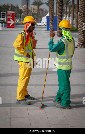 Two building workers talking to each other on a building site in Dubai, UAE - Stock Photo