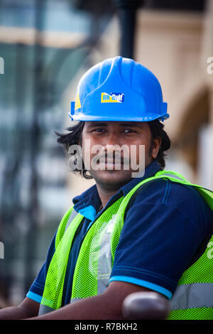 Construction Worker wearing a Hard Hat Safety helmet on a construction site in Dubai,UAE - Stock Photo