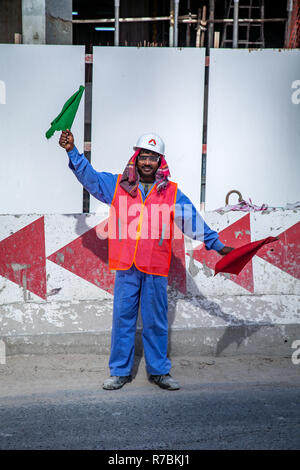 Construction site traffic controller waves flags on building site in Dubai, UAE - Stock Photo