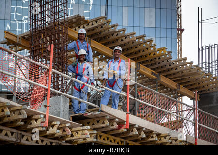 Three building workers up on scaffold on building site in Dubai - Stock Photo