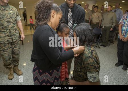 U.S. Marine Corps Sgt. Yahmise D. Bordies, administrative specialist, Plans, Policies and Operations, is pinned on by her two daughters during her promotion ceremony at the Pentagon, Arlington Va., May 05, 2017. Bordies was promoted to the rank of Staff Sergeant. - Stock Photo