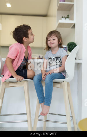 cute little brother and sister at home barefoot in kitchen having fun - Stock Photo