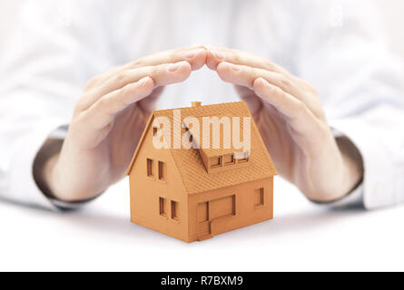 Small orange house protected by hands - Stock Photo