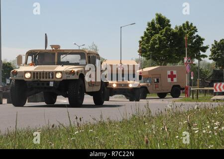 A High Mobility Multipurpose Wheeled Vehicle (HMMWV) and two military ambulances depart in a convoy from Nuremberg Airport, Germany on May 16, 2017. The vehicles are from the 2nd Battalion, 12th Infantry Regiment, 2nd Infantry Brigade Combat Team, 4th Infantry Division, which is on an emergency deployment readiness exercise to show the world the U.S. Army's readiness to deploy at a moment's notice. ( - Stock Photo