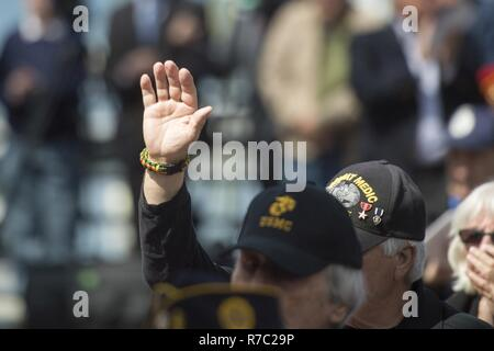 A Vietnam veteran raises his hand during the 30th Annual Vietnam Remembrance and Wreath Laying Ceremony held at the Vietnam Veterans Memorial Clock Tower in Quincy, Mass. April 27, 2017. Each year, the names of the 48 Quincy residents who died during the Vietnam War are read during a memorial roll call at the clock tower. (Dept. of Defense - Stock Photo
