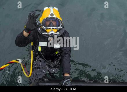 U.S. Navy Equipment Operator 3rd Class Thomas Dahlke, Underwater Construction Team 2, enters the water during an underwater surface-supply dive in support of Balikatan 2017 at Ipil Port in Ormoc City, Leyte, May 12, 2017. The surface-supply dive training prepares Philippine and U.S. service members to clear debris in ports and open up supply lines for victims of natural disasters and crises. - Stock Photo