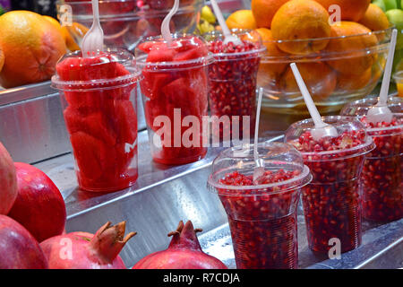 Pieces of fresh fruit and berries of a pomegranate in plastic cups on the counter. Fresh, healthy snacks are sold at a market in Jerusalem, Israel. - Stock Photo