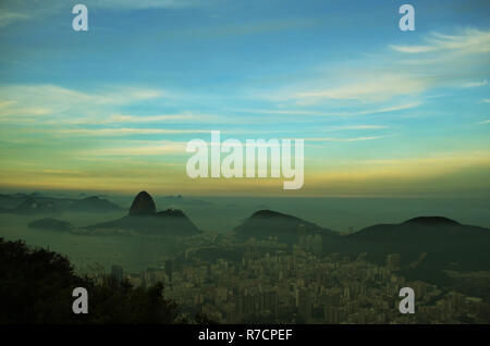 Spectacular aerial view over Rio de Janeiro as viewed from Corcovado. The famous Sugar Loaf peak sticks out of Guanabara Bay. Sugar Loaf Mountain seen - Stock Photo