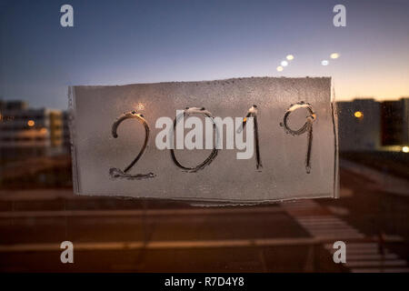 written the number of the new year 2019 on a window with a spray of foam at night in the light of the streetlights - Stock Photo